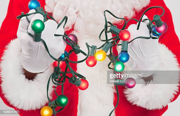 Santa Claus holding colored Christmas lights