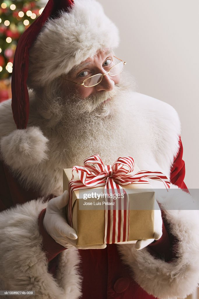 Santa Claus holding gift, smiling, portrait, close-up : Stockfoto