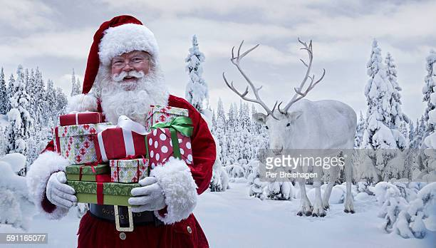Santa Claus holding gifts with a reindeer