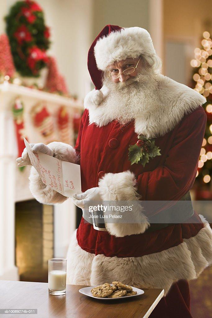 Santa Claus holding letter, smiling, portrait : Stockfoto