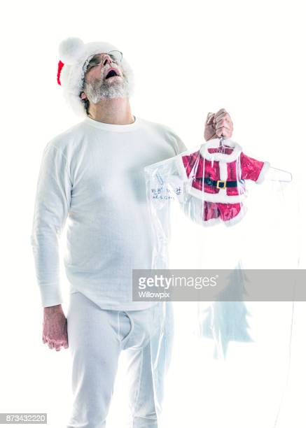 santa claus holding shrunken dry cleaned santa costume in disbelief - santa face stock photos and pictures