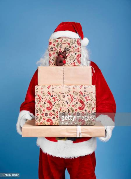 santa claus holding stack of christmas gifts. debica, poland - santa face stockfoto's en -beelden