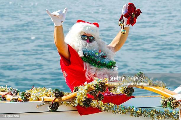santa claus in canoe flashing shaka - hawaii christmas stock pictures, royalty-free photos & images