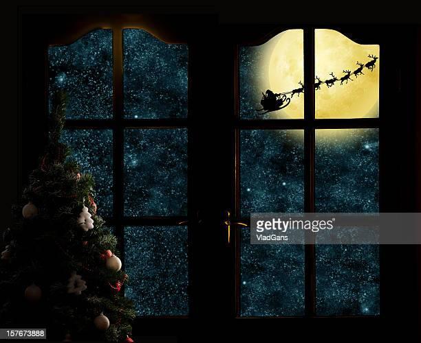 Santa Claus in his deer sled near the moon