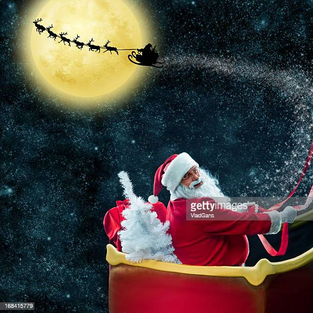 santa claus in his deer sled near the moon - sleigh stock photos and pictures