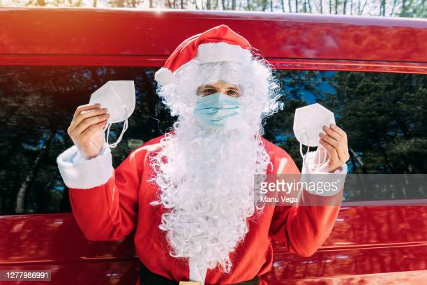 santa claus in medical mask showing what to wear masks looking at the camera - father christmas stock pictures, royalty-free photos & images