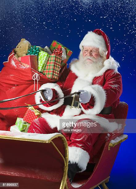 santa claus in sleigh with bag of toys - babbo natale slitta foto e immagini stock