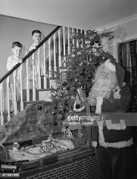 santa claus inserting gift in christmas stocking and boys standing on staircase - {{ contactusnotification.cta }} stockfoto's en -beelden