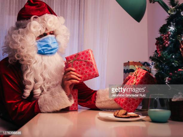santa claus inside a house with face mask, milk and cookies putting gifts on christmas tree - father christmas stock pictures, royalty-free photos & images