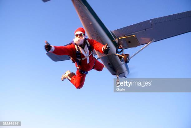 santa claus jumping from the plane - christmas plane stock pictures, royalty-free photos & images