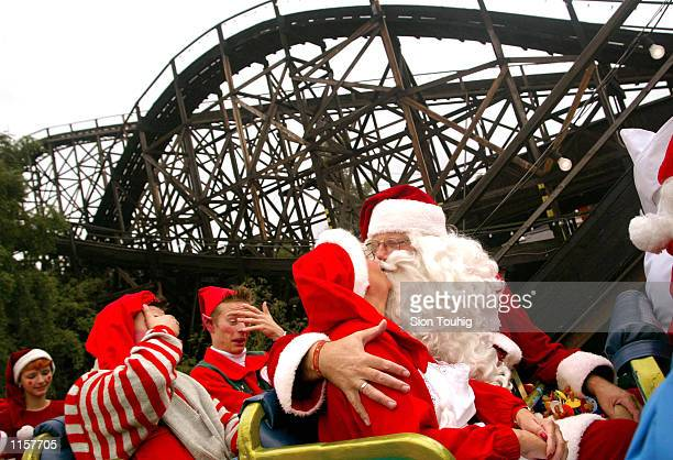 Santa Claus kisses Mrs Claus as they ride a rollercoaster at the 'Bakken' amusement park during the 39th World Santa Claus Congress July 23 2002 in...