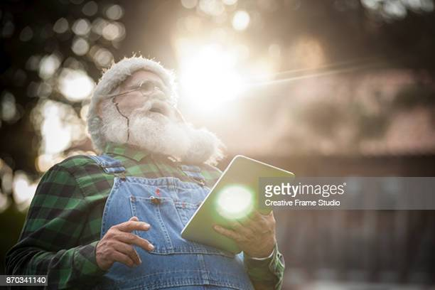 Santa Claus laughing while holding his digital tablet in front of his log cabin in the woods