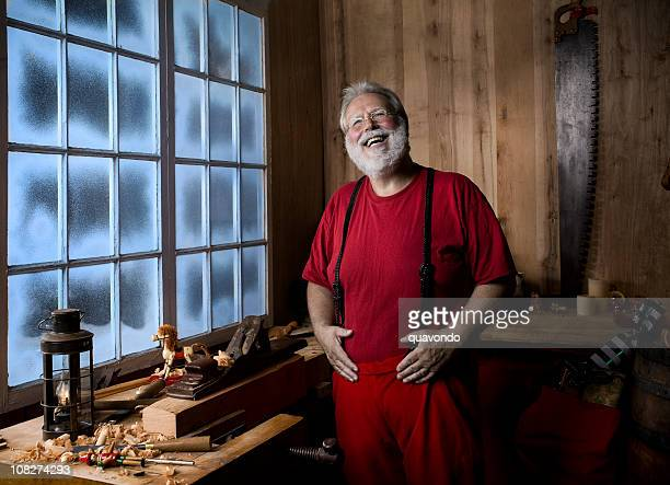 cheerful santa claus laughing in christmas workshop, hands on belly - santas workshop stock photos and pictures