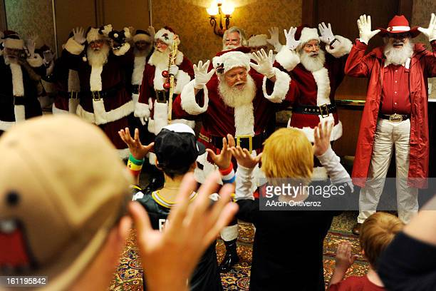 Santa Claus leads a group of children in the singing of Rudolph the Red Nosed Reindeer during a Santa Claus School graduation ceremony at the Red...
