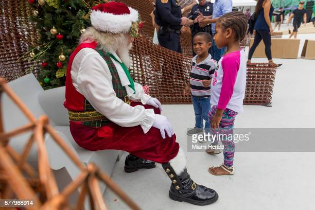 Santa Claus left talks to Keon Kamaal center and his sister Kazaria Kamaal during the 10th annual Feed a Friend event hosted by Gloria and Emilio...
