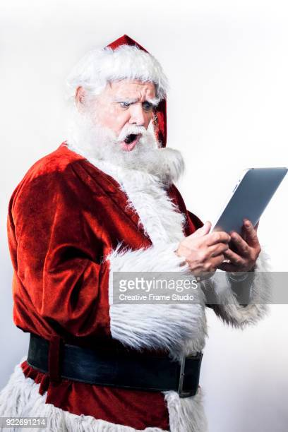 Santa Claus looking amazed at a digital tablet
