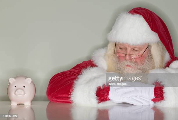 Santa Claus looking at piggy bank
