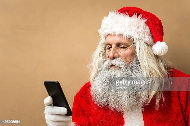 santa claus mirando teléfono inteligente