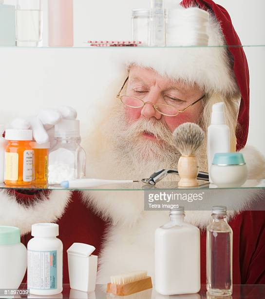Santa Claus looking in medicine cabinet