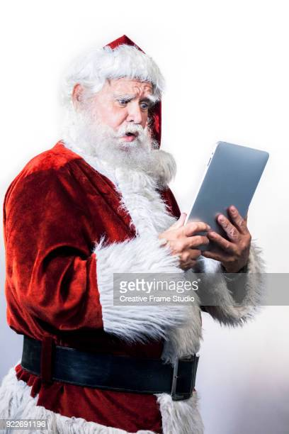 Santa Claus looking with surprise at a digital tablet