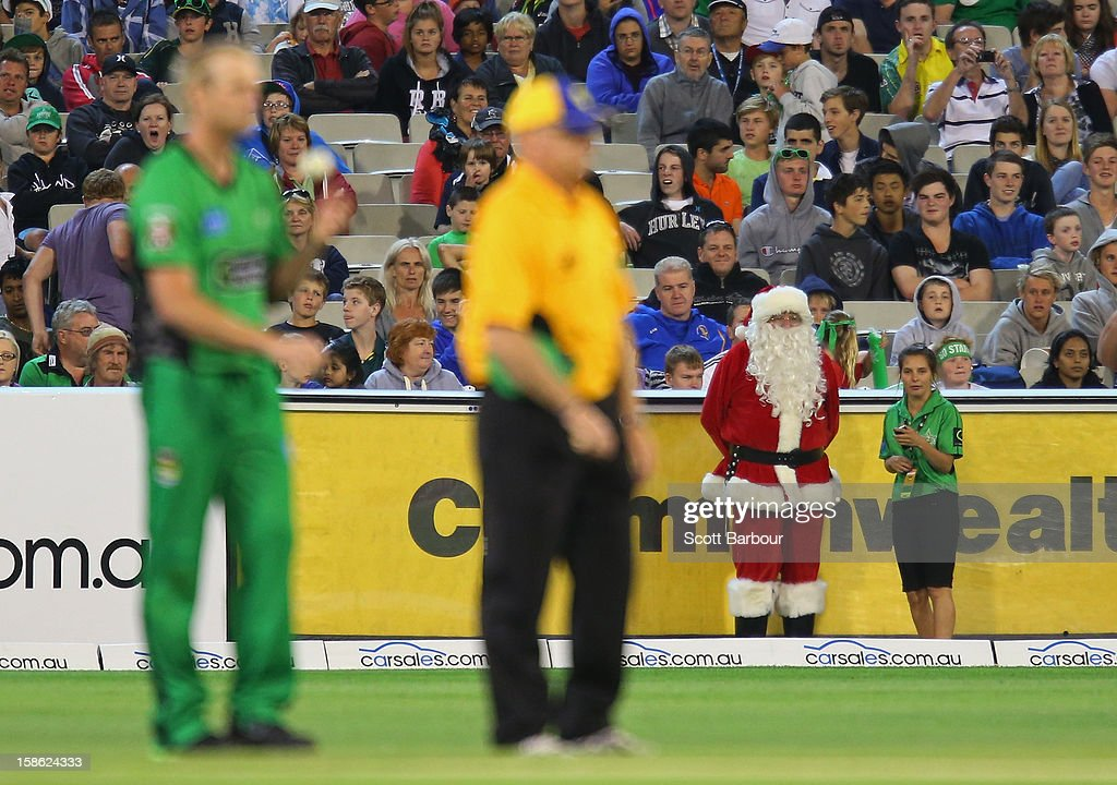 Santa Claus looks on from the boundary as Cameron White of the Stars prepares to bowl during the Big Bash League match between the Melbourne Stars and the Sydney Sixers at Melbourne Cricket Ground on December 21, 2012 in Melbourne, Australia.