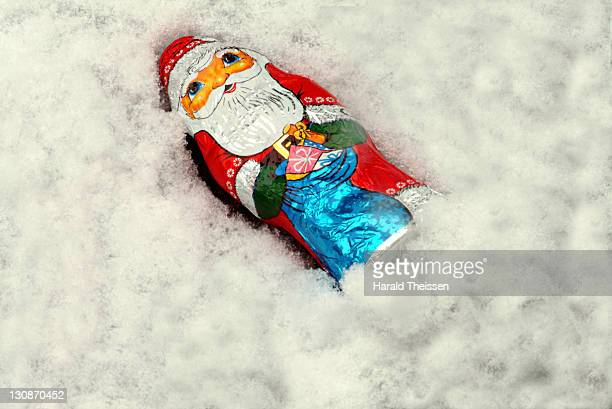 Santa Claus made of chocolade lying in snow