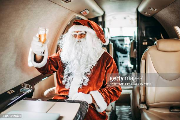 santa claus making a toast with a champagne glass while sitting aboard a private airplane - christmas plane stock pictures, royalty-free photos & images