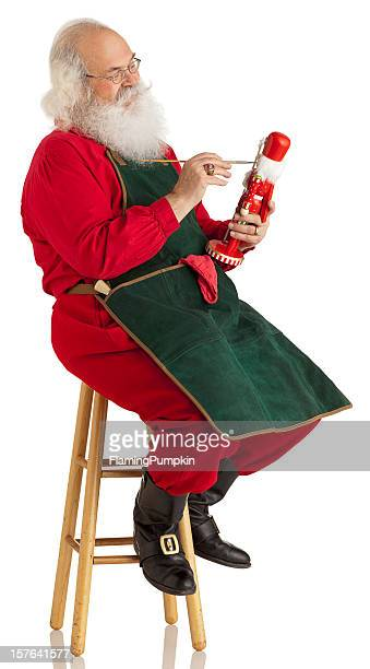 Santa Claus making toys on a White. Vertical. XL