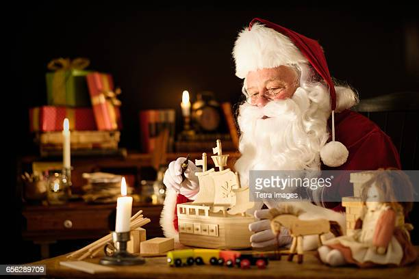 Santa Claus making wooden toy