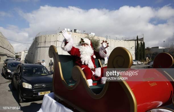 A Santa Claus on his sleigh precedes the convoy of Latin Patriarch of Jerusalem Pierbattista Pizzaballa passing near the controversial Israeli...