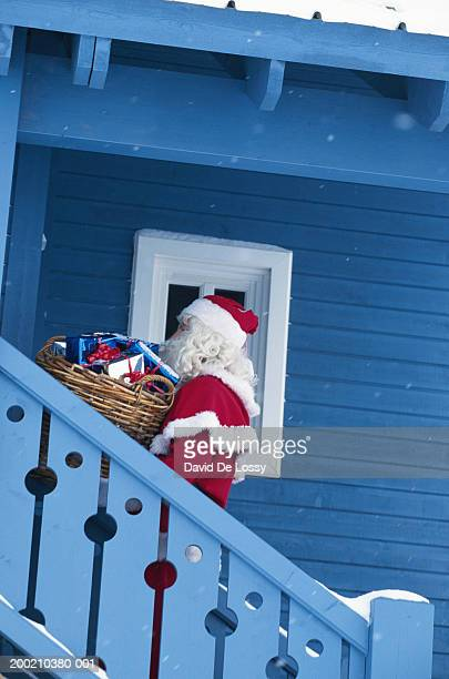Santa Claus on stairs of house with gifts