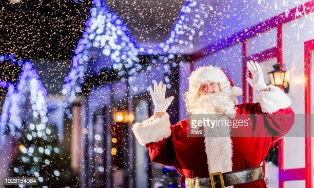 santa claus on village street at night, waving - florida christmas stock pictures, royalty-free photos & images