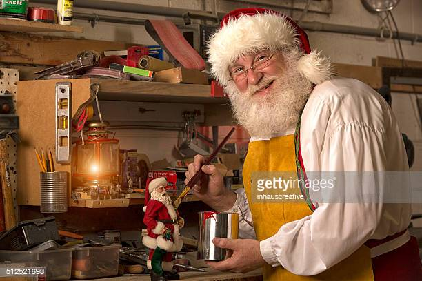 santa claus painting a doll in his workshop - santas workshop stock photos and pictures