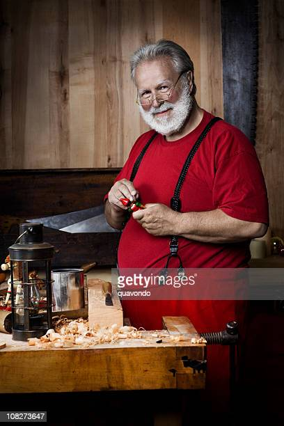 cheerful santa claus in workshop painting toy, copy space - santas workshop stock photos and pictures