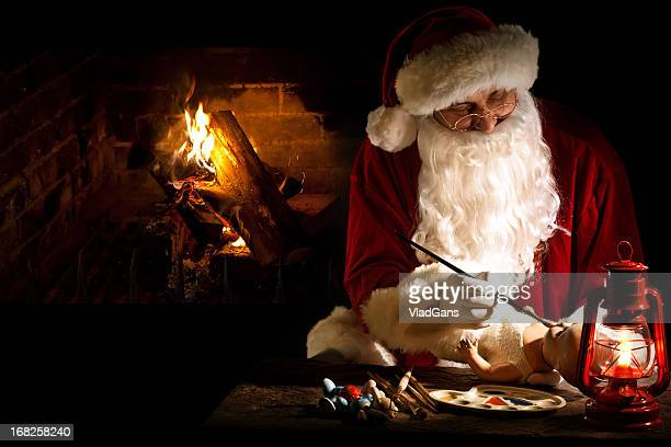 santa claus painting a toy - santas workshop stock photos and pictures