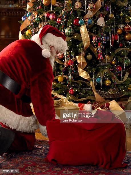 Santa Claus Placing Presents at Christmas Tree