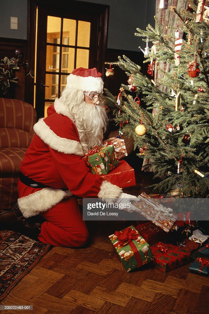 Santa claus placing presents under christmas tree in Photoshop santa in your living room free