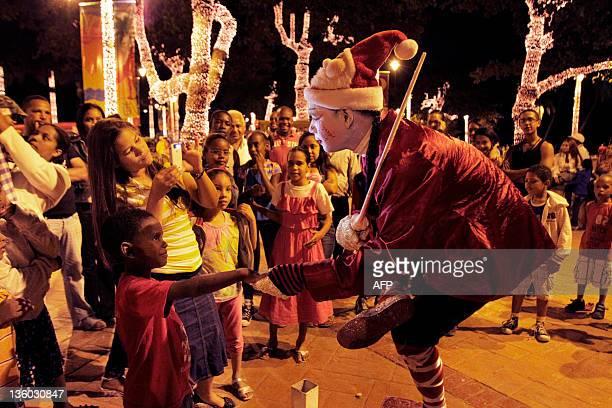 A Santa Claus plays with children of Santo Domingo on December 20 2011 AFP PHOTO/ERIKA SANTELICES