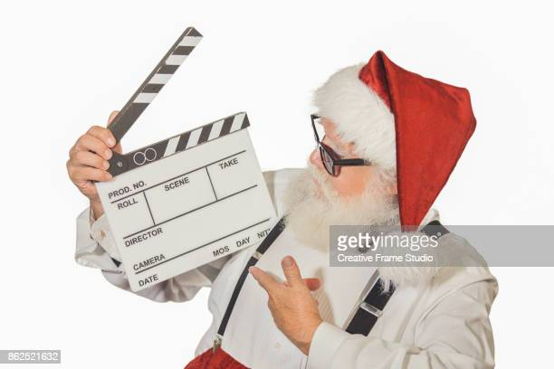 Santa Claus pointing and looking a film clapperboard with a vital and welcome attitude wearing sunglasses a white shirt with suspenders