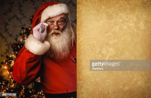 Santa Claus pointing near wall