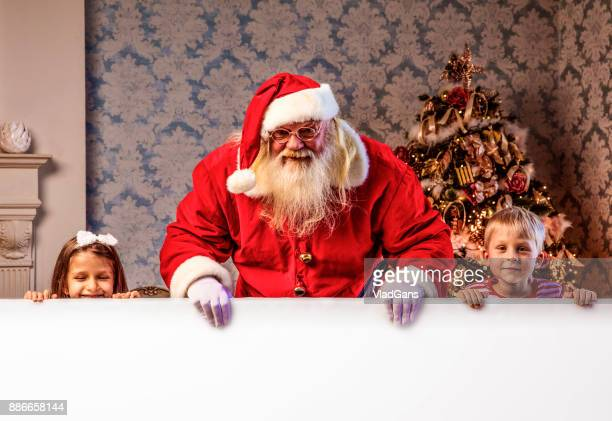 Santa Claus pointing on blank banner