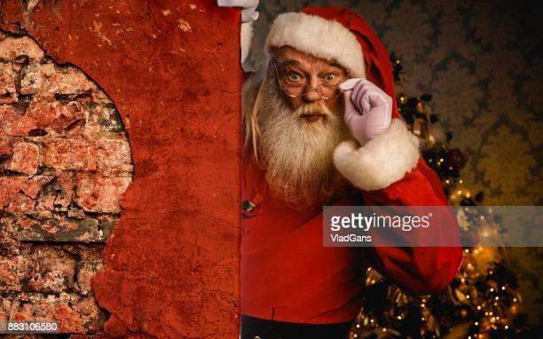 Santa Claus pointing on brick wall