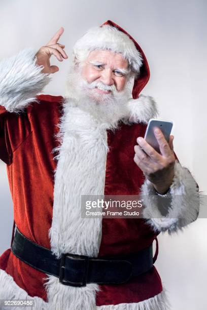 Santa Claus pointing up with his finger and holding a smartphone