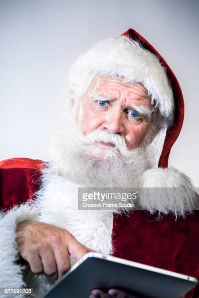 Santa Claus pointing with his finger a digital tablet and looking at camera