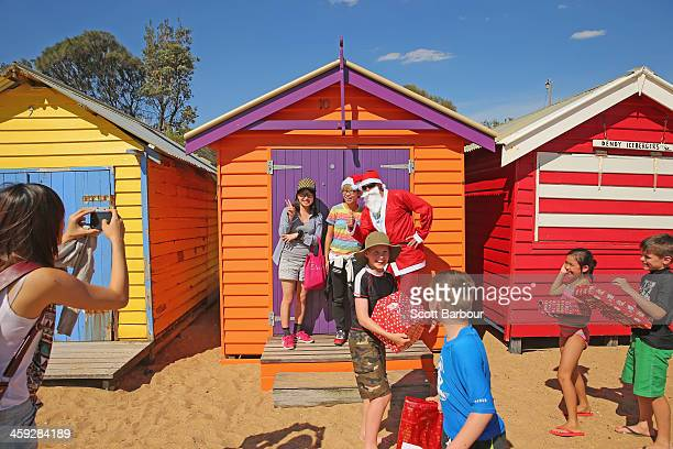 Santa Claus poses for a photo as he helps children open their Christmas presents on Christmas Day at Brighton Beach on December 25 2013 in Melbourne...