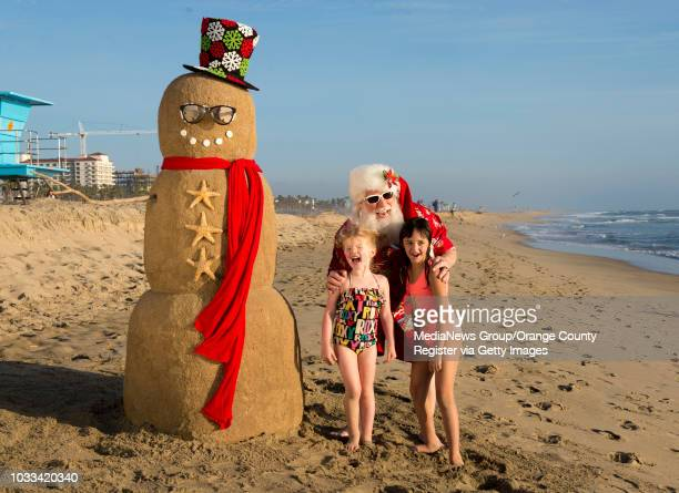 Santa Claus poses for a photo with Eden Wenger left and her friend Elsie Ensor who were at the beach during the Orange County Register's annual...