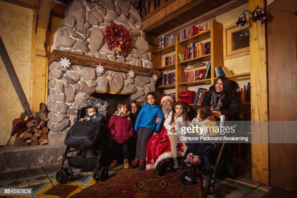 Santa Claus poses with a family in his house in the Reggia of Venaria on December 2 2017 in Turin Italy