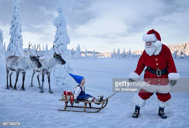 Santa Claus pulling a girl on sled with reindeer