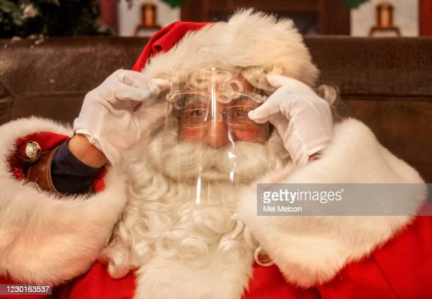 Santa Claus, puts on a protective shield against the coronavirus, before meeting and being photographed at a safe distance with children at Santas...