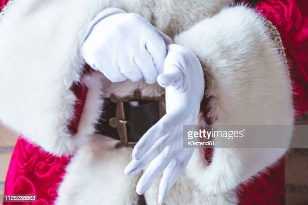 santa claus putting on his white gloves, close-up - santa close up stock pictures, royalty-free photos & images